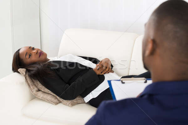 Woman Laying On Couch In Front Of Psychiatrist Stock photo © AndreyPopov
