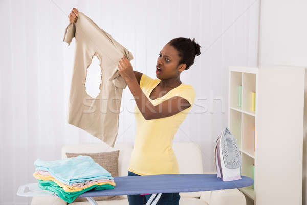 Woman Looking At Iron Burned Cloth Stock photo © AndreyPopov