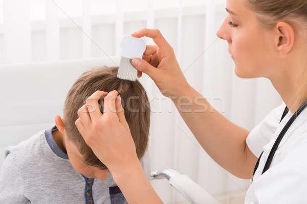 Doctor Doing Treatment On Boy's Hair Stock photo © AndreyPopov