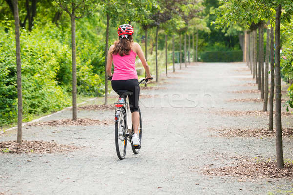 Female Cyclist Riding Away On Bicycle Stock photo © AndreyPopov
