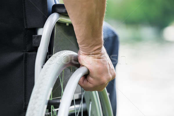 Disabled Man Pushing Wheel Of Wheelchair Stock photo © AndreyPopov