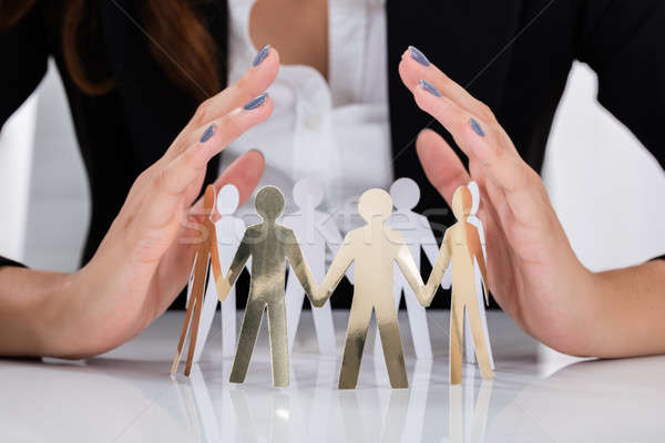 Businesswoman Hand Protecting Cut-out Figures Stock photo © AndreyPopov