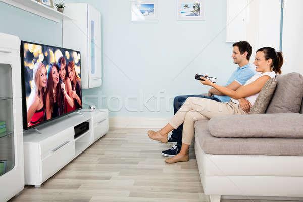 Сток-фото: пару · сидят · диван · Смотря · телевизор · телевидение