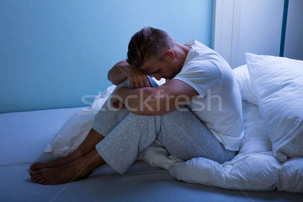 Stock photo: Sad Man Sitting On Bed