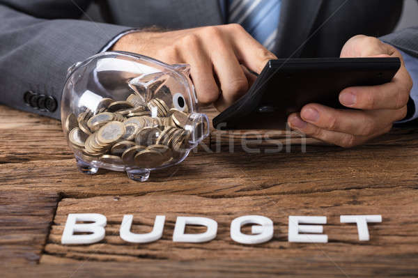 Stock photo: Businessman Calculating Budget By Piggybank At Table