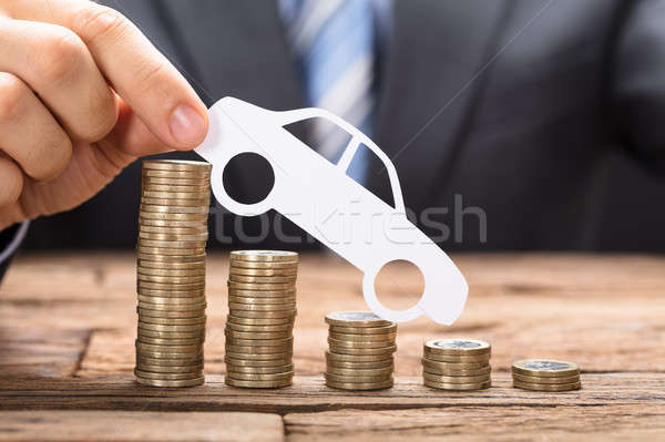 Holding Paper Car On Coins Arranged In Declining Order Stock photo © AndreyPopov