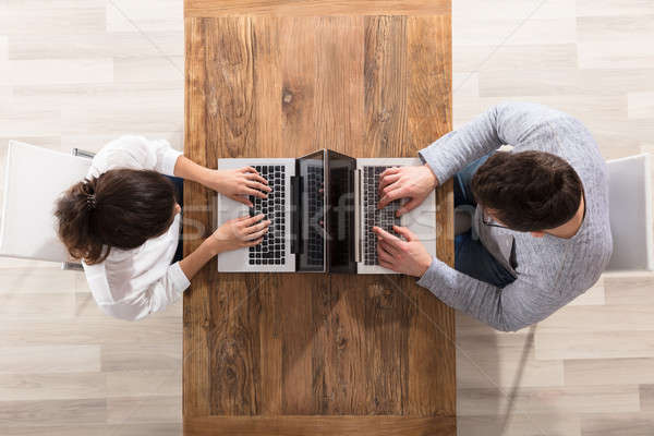 Kilátás pár laptopot használ ül szemtől szembe asztal Stock fotó © AndreyPopov
