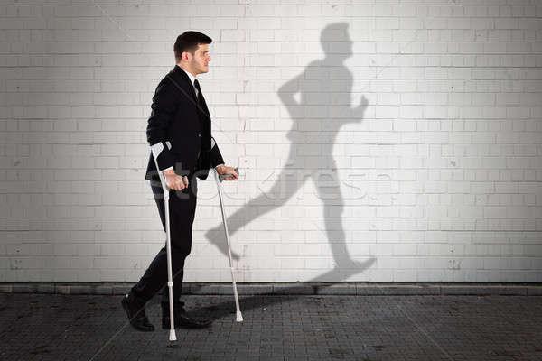 Shadow Of Man On Wall With Businessman Walking On Sidewalk Stock photo © AndreyPopov