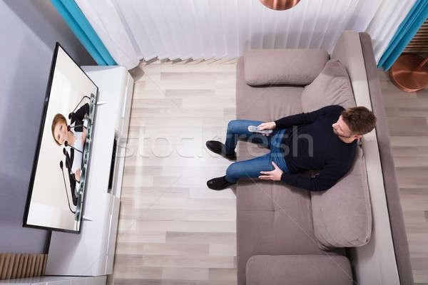 Férfi tv nézés otthon fiatalember ül kanapé Stock fotó © AndreyPopov