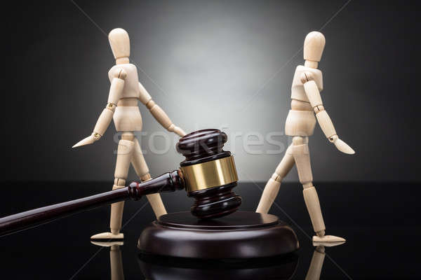 Gavel In Front Of Wooden Dummy Standing Against Each Other Stock photo © AndreyPopov