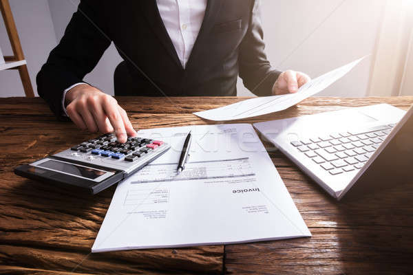 Businessperson's Hand Calculating Invoice In Office Stock photo © AndreyPopov