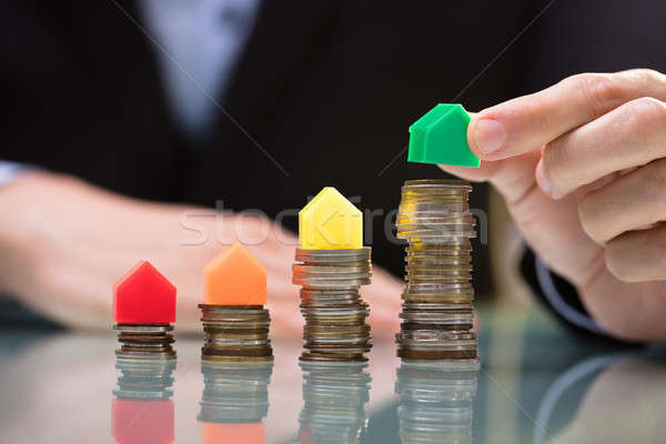 Businessperson Placing Green House Model On Top Of Stacked Coins Stock photo © AndreyPopov