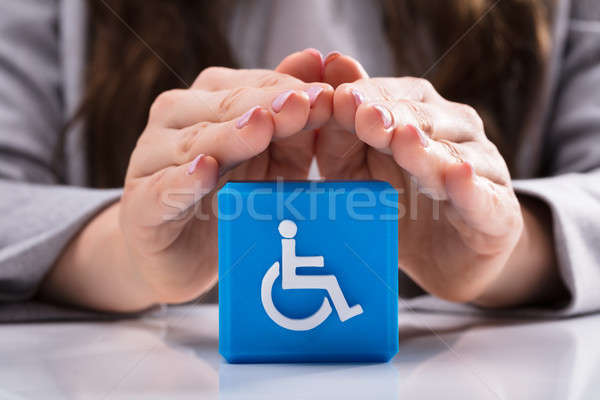 Woman Protecting Cubic Block With Disabled Handicap Icon Stock photo © AndreyPopov