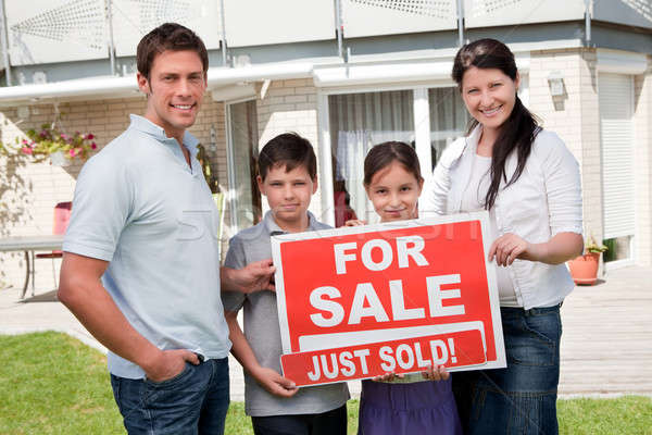 Stock photo: Family with a sale sign outside their new home