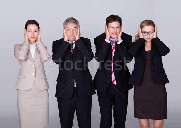 Négy üzletemberek tart fülek sokoldalú áll Stock fotó © AndreyPopov