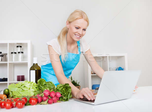 Cheerful young woman cooking Stock photo © AndreyPopov