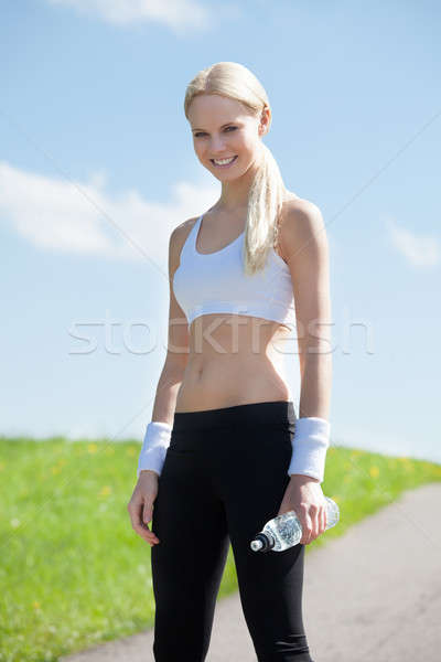 Happy Young Woman Holding Water After Jogging Stock photo © AndreyPopov