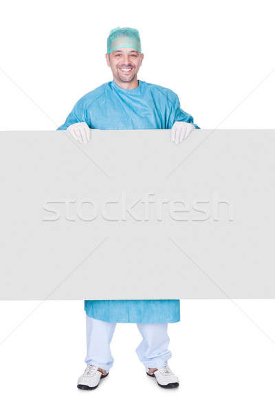 Doctor In Operation Gown Holding Blank Placard Stock photo © AndreyPopov