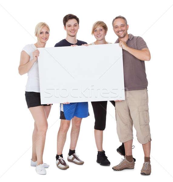 Happy family holding blank placard Stock photo © AndreyPopov