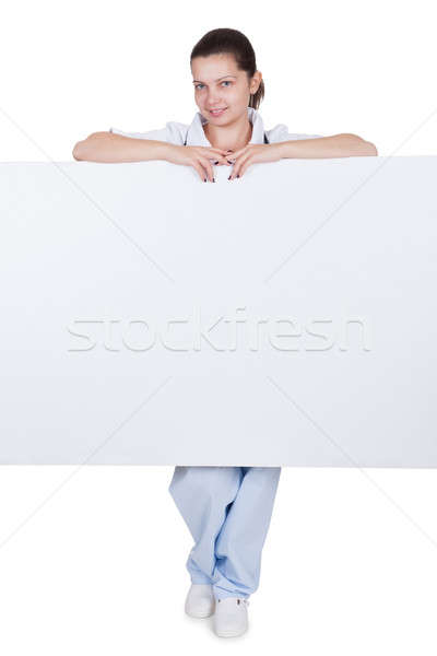 Doctor or nurse with blank signboard Stock photo © AndreyPopov