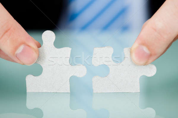 Stock photo: Businessman Joining Puzzle Pieces