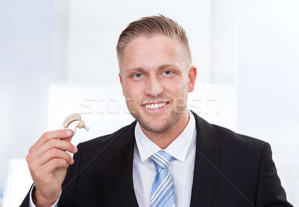 Businessman holding hearing aid Stock photo © AndreyPopov