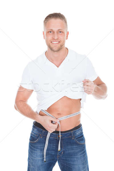 Healthy fit young man lifting up his white t-shirt Stock photo © AndreyPopov