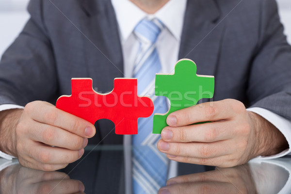 Businessman Fitting Two Puzzle Pieces Together Stock photo © AndreyPopov