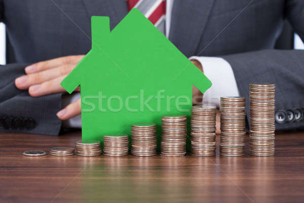 Businessman With Coin Stacks By House Model At Desk Stock photo © AndreyPopov
