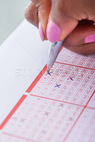 Woman's Hand Marking Numbers On Lottery Ticket Stock photo © AndreyPopov