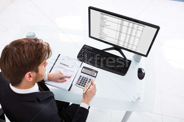 Businessman Calculating Expenses At Office Desk Stock photo © AndreyPopov