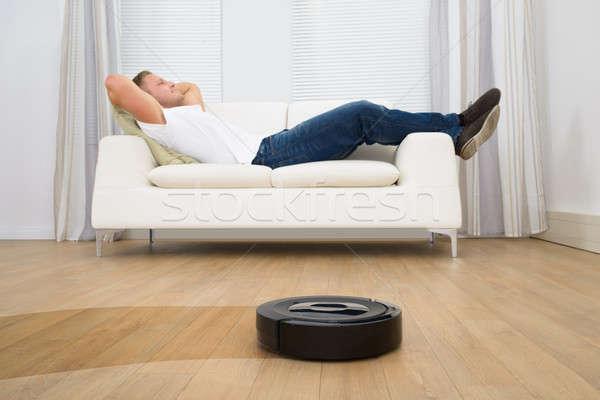 Robotico aspirapolvere uomo rilassante divano Foto d'archivio © AndreyPopov
