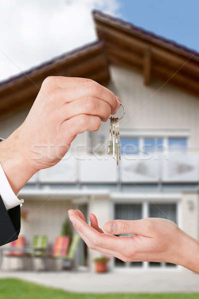 Real Estate Agent Giving Keys To Owner Against New House Stock photo © AndreyPopov