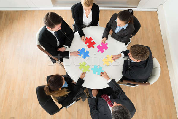 Businesspeople Holding Multi-colored Jigsaw Puzzle Stock photo © AndreyPopov
