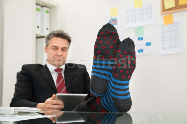 Businessman With Socks In His Feet Using Digital Tablet Stock photo © AndreyPopov