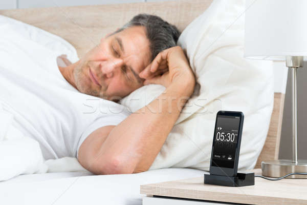 Man On Bed With Alarm On A Cell Phone Display Stock photo © AndreyPopov