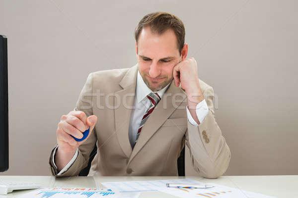 Businessman Squeezing Blue Stressball Stock photo © AndreyPopov