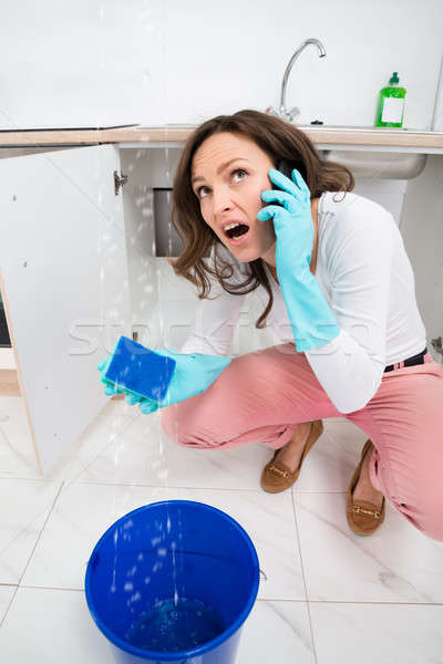 Woman Calling To Plumber Through Mobile Phone Stock photo © AndreyPopov