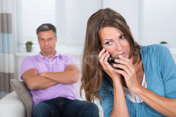 Woman Talking On Mobile Phone In Front Of Her Husband Stock photo © AndreyPopov