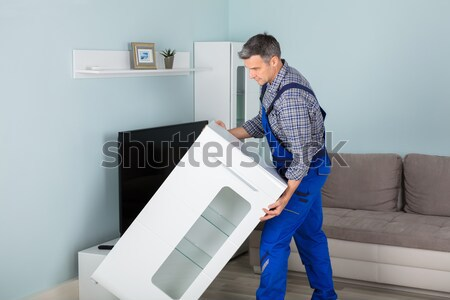 Stock photo: Happy Technician With TV Set Top Box At Home