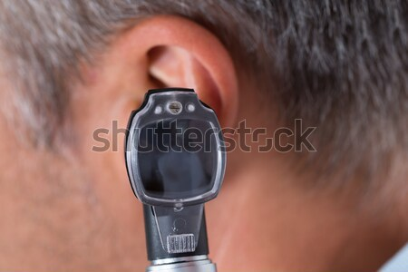 Doctor Checking Ear Of Male Patient Stock photo © AndreyPopov