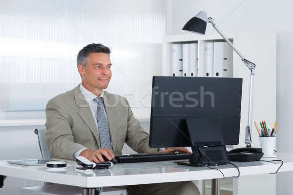 Confident Businessman Using Computer At Desk Stock photo © AndreyPopov