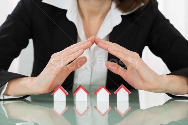 Businesswoman Hand Sheltering House Models Stock photo © AndreyPopov