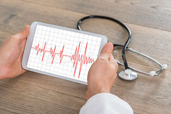Male Doctor Showing Heartbeat On Digital Tablet Stock photo © AndreyPopov