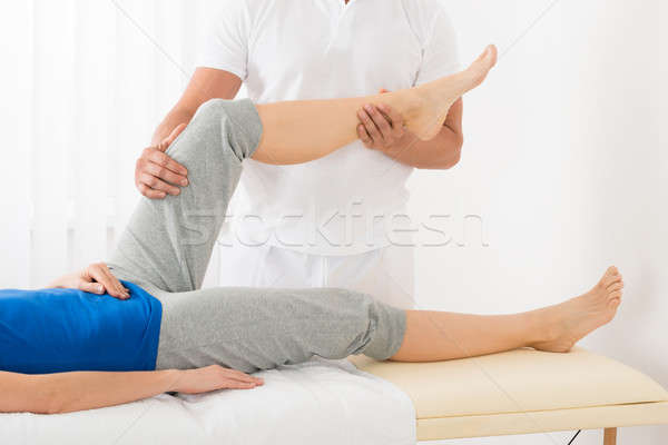 Masseur Giving Leg Massage To Woman Stock photo © AndreyPopov