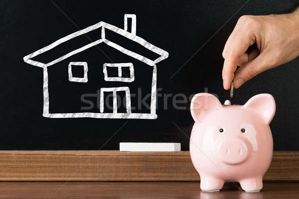 Person Saving Money In Piggybank For Purchasing House Stock photo © AndreyPopov
