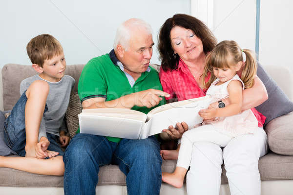 Grandparent And Grandchildren Looking At Photo Album Stock photo © AndreyPopov