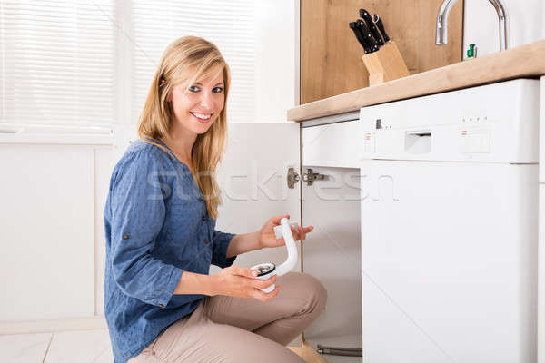 Woman Holding Sink Pipe In Kitchen Stock photo © AndreyPopov