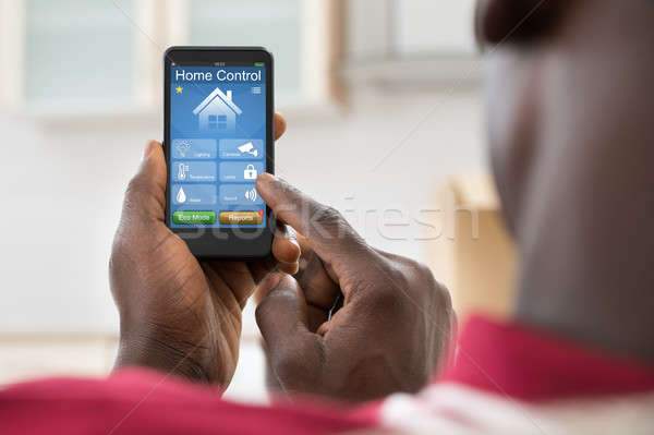 Man Using Home Control System On Mobilephone Stock photo © AndreyPopov