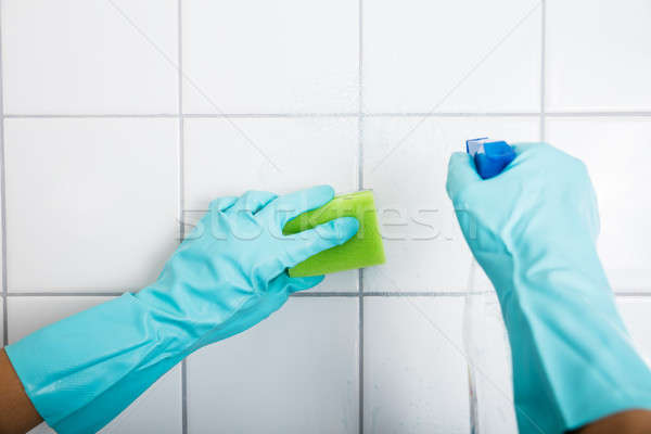 Close-up Of Person Cleaning The Tiled Wall Stock photo © AndreyPopov